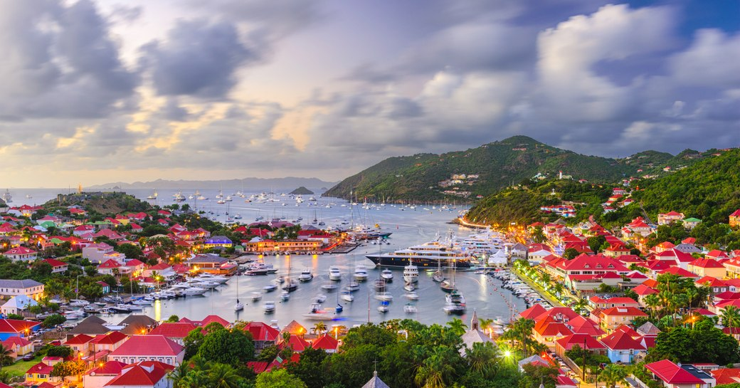 Panoramic view over St Barts in Caribbean showing hills, houses and harbour under a cloudy sky.