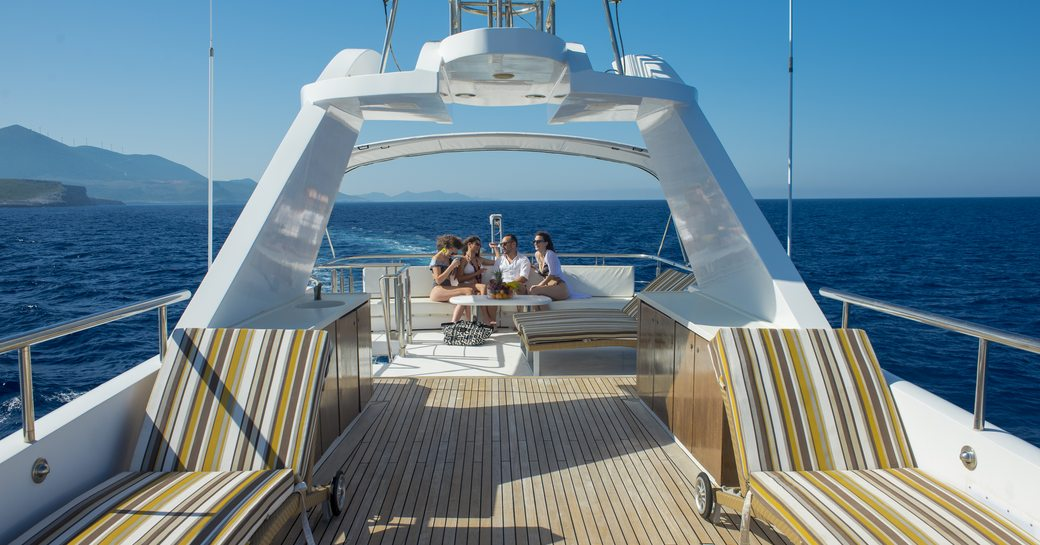 a group of friends enjoying the sun and panoramic view from the capacious and airy sun deck of charter yacht carmen fontana