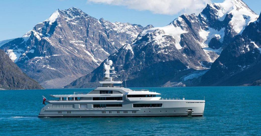 Expedition yacht CLOUDBREAK cruising against a mountainous backdrop