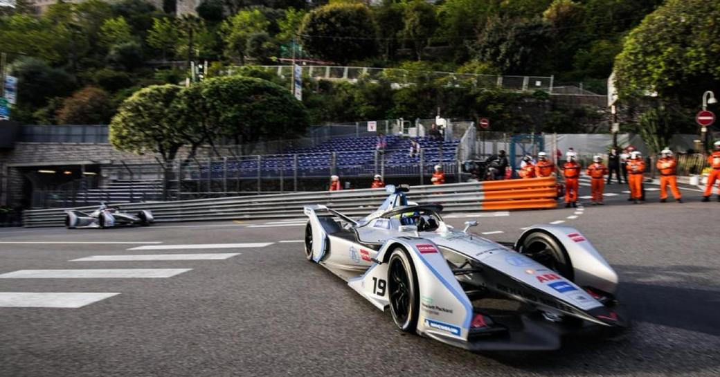 Frontal view of Formula E car sat on track, with green foliage in background.