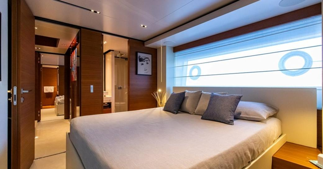 Guest cabin onboard Ferretti yacht charter 30m PENELOPE, central berth and view through doors to opposite cabin