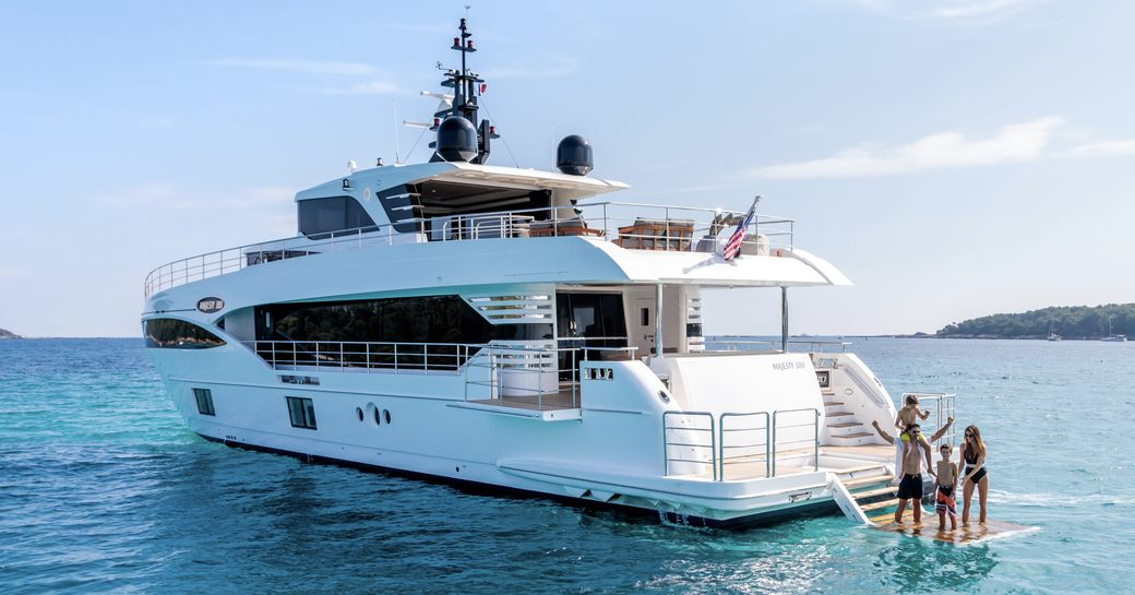 charter guests on submersible swim platform of motor yacht ONEWORLD