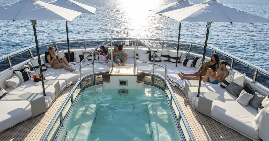 Charter guests sunbathing on Roma yacht sundeck in France