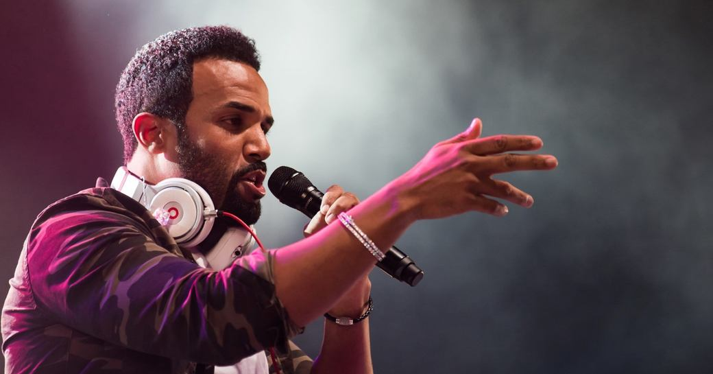 Craig David wearing headphones around neck performs holding a microphone