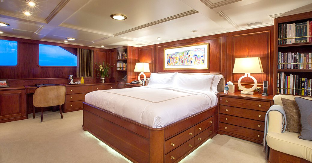 the capacious and sophisticated master suit with desk and vanity illuminated by deicreet lighting inside charter yacht Lady J