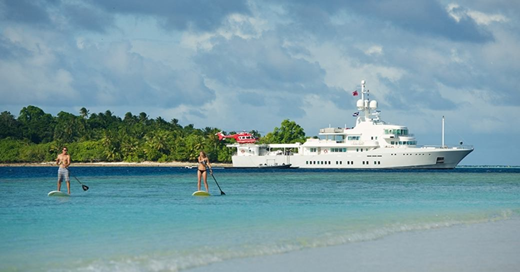 Superyacht SENSES anchors at charter guests play on stand-up paddle boards