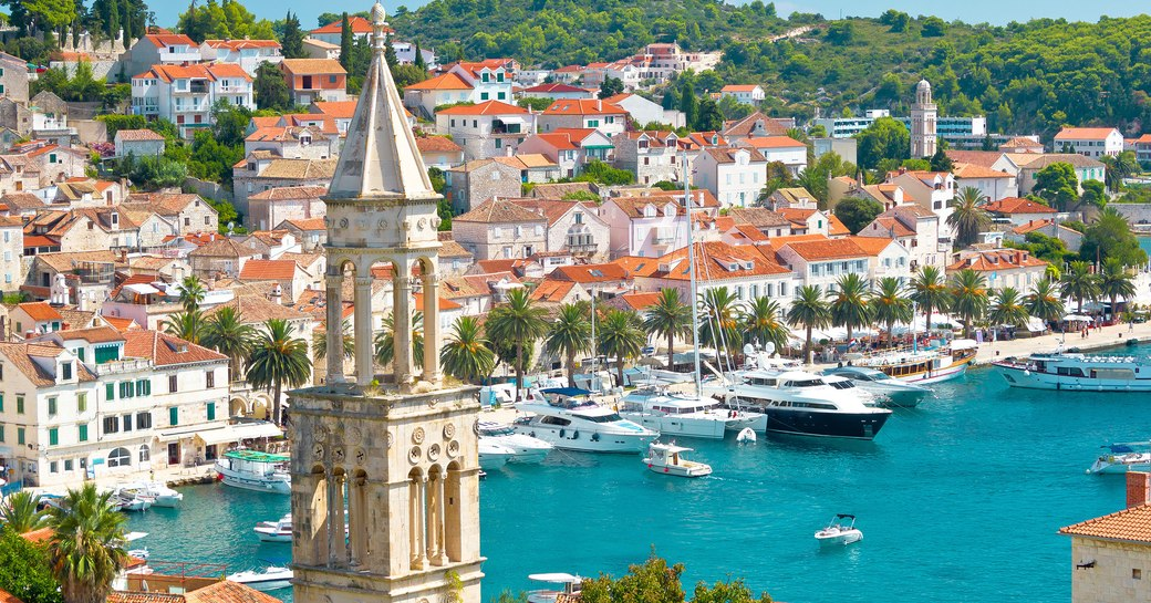 Turquoise bay in Croatia, with yachts lined up along the harbour
