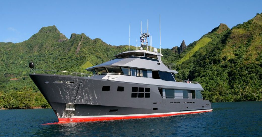 Superyacht AKIKO sits at anchor a short distance from a green coast