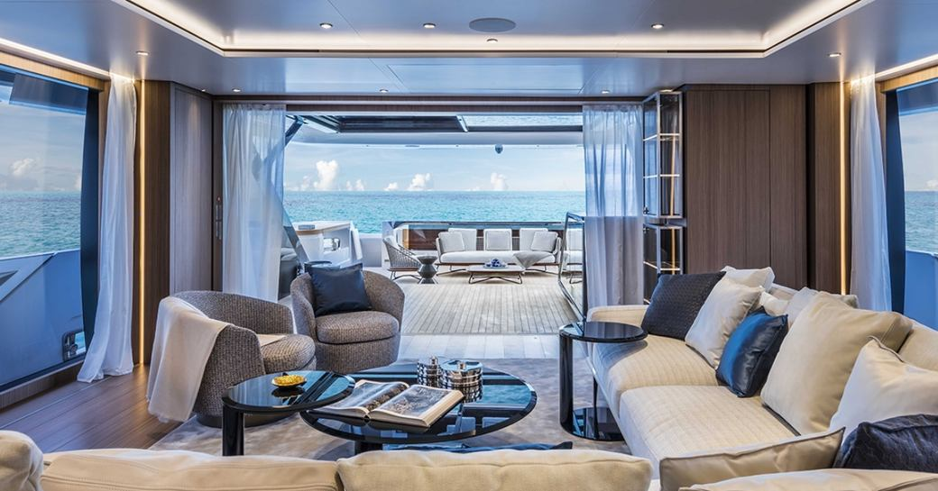 sumptuous seating area in the main salon of luxury yacht Vista Blue looking out onto aft deck