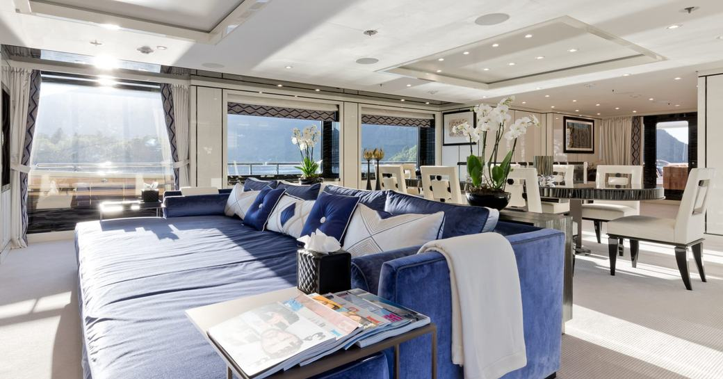 sumptuous blue sofa in the full-length window-flanked main salon of superyacht LILI