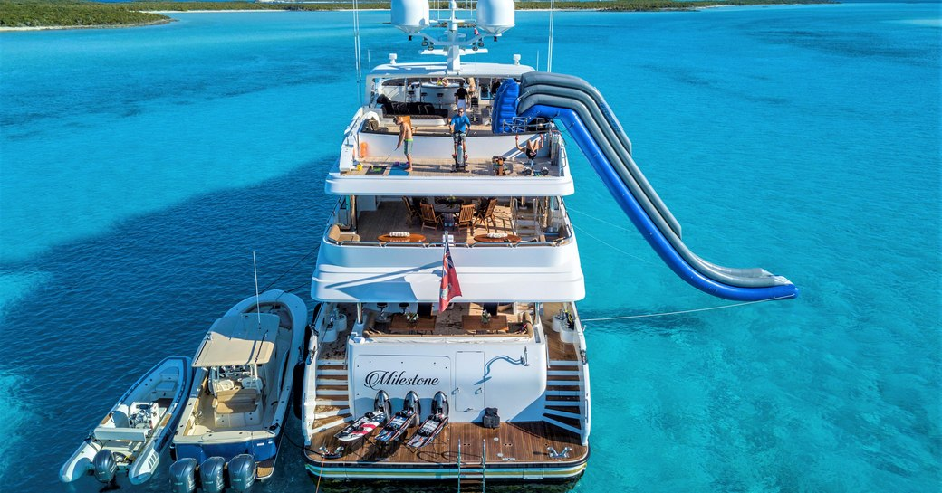 Superyacht Milestone at anchor in the Caribbean, with water slide going into the sea