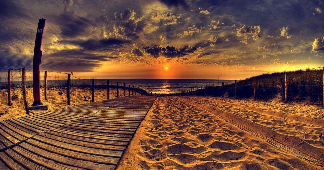 sun sets over golden sand beach in Ibiza