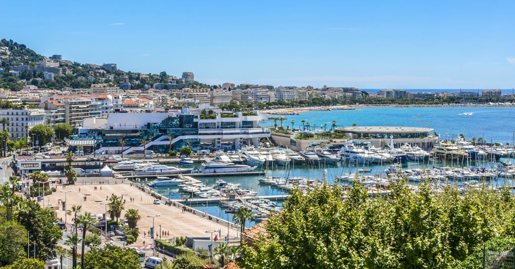 Overview of Cannes marina, with multiple yachts moored in berths, surrounded by sea.