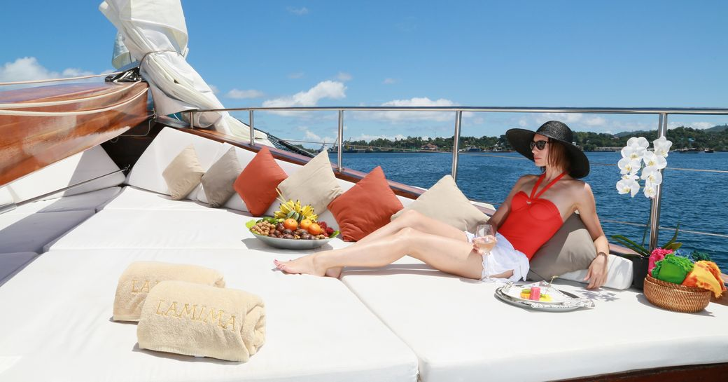 A charter guests reclines on the sunpads of a sailing yacht