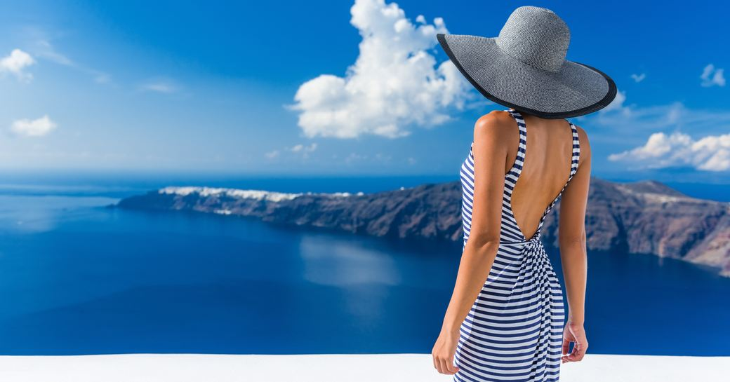a beautiful woman overlooks the mediterannean sea while on her luxury yacht charter