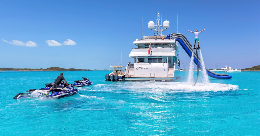 Superyacht MILESTONE at anchor, with charter guest using the Hoverboard and another guest on the Jet-Skis