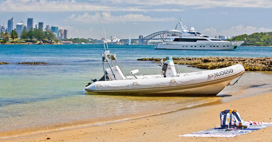 motor yacht Oscar II' anchors in a quiet bay against the backdrop of Sydney's cityscape