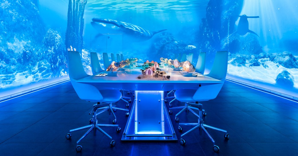 Table in Sublimotion, restaurant in Ibiza, with videos playing on the walls showing an underwater seascape