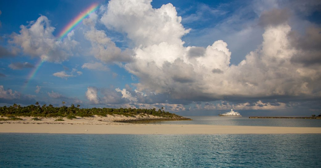 Superyacht DREAM below a rainbow, chartering in the South Pacific