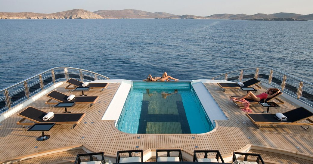 Model basking in the sunlight by the infinity pool of luxury superyacht Alfa Neroa