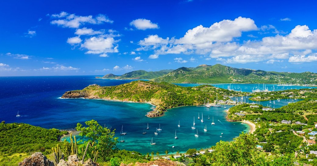 Sailing yachts and motor yachts cruising in the bright blue waters of Antigua
