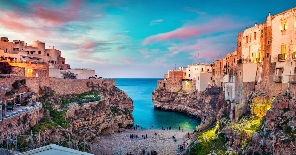 little beach and tall buildings and blue cove in eastern italy, puglia region, Polignano a Mare