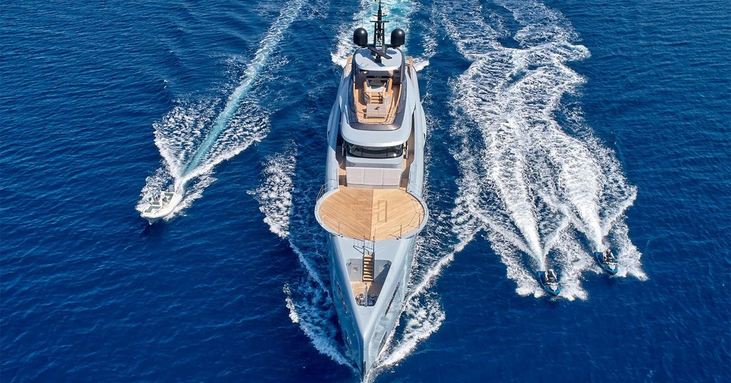 superyacht geco while underway, foredeck helipad and tenders alongside