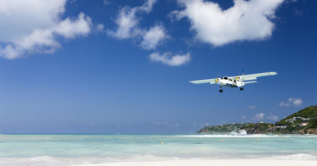 small chartered flight/ private plane arriving into the caribbean above sandy beach and blue sea