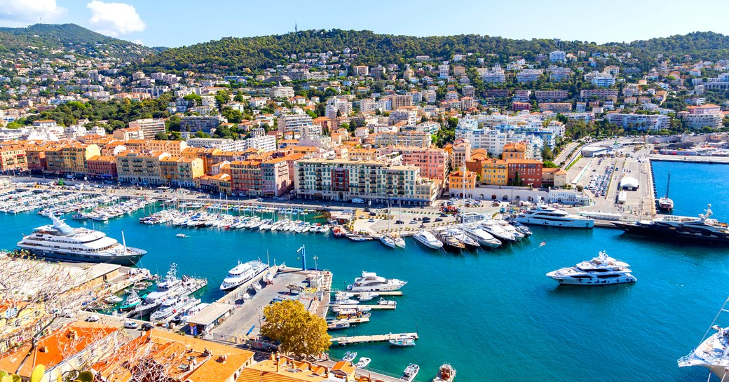 a busy marina in Nice with many superyachts arriving for their luxury yacht charter adventure through the Mediterranean