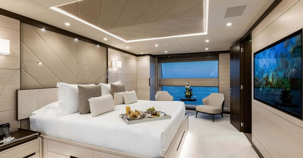 owners suite on board benetti yacht jacozami, with beautiful wide windows and large white bed