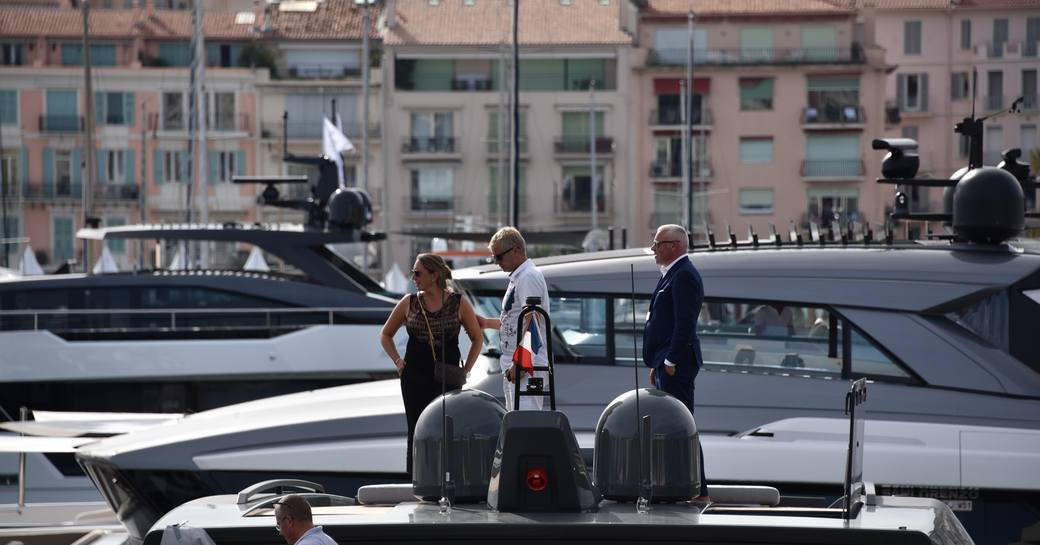 woman stands on the deck of a yacht in cannes during the boat show