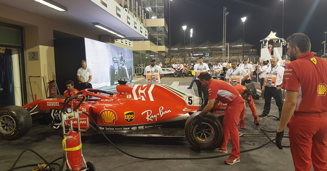 Formula 1 race car in pits, surrounded by crew
