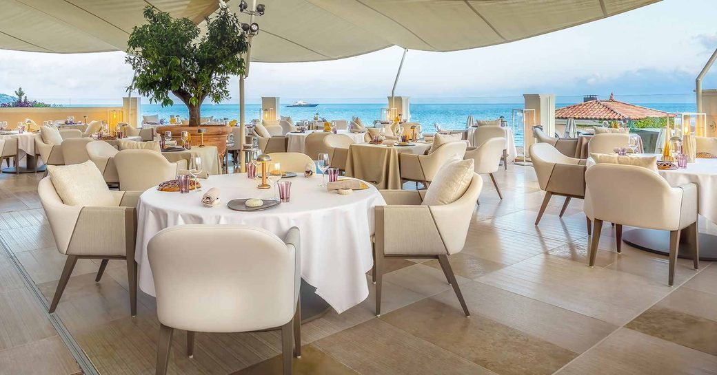 terrace of blue bay restaurant in monaco, with balcony overlooking the ocean and white shading above the tables