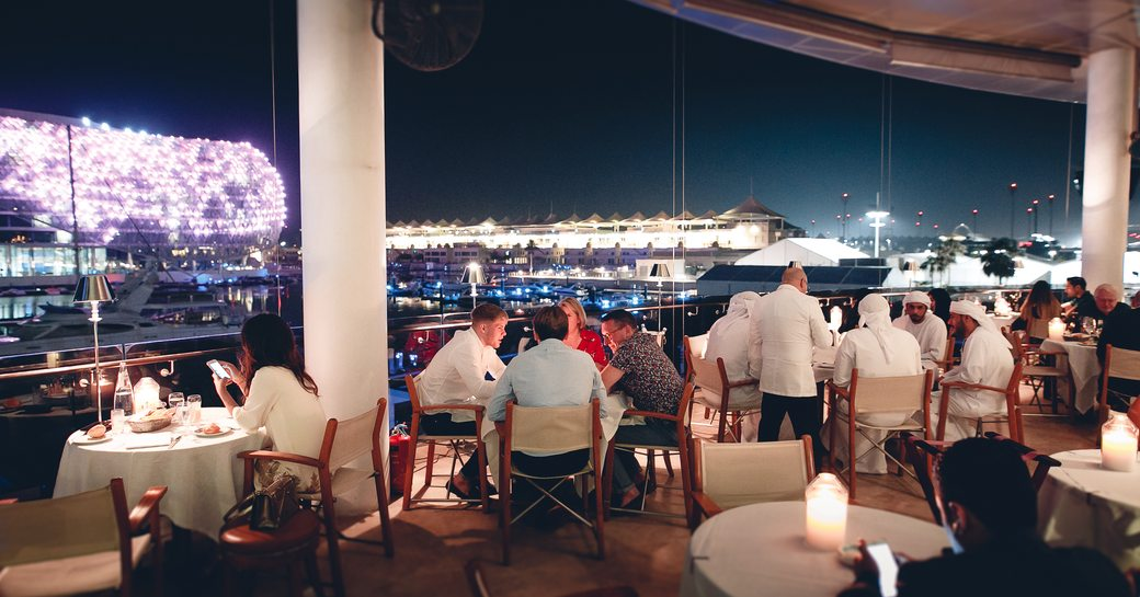 guests sit at tables spread across the terrace of restaurant Cipriani with views across Yas Marina in Abu Dhabi