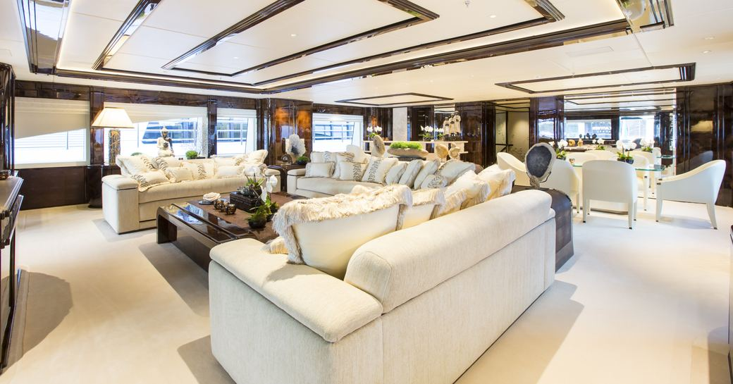 main salon with sumptuous sofa and formal dining area on board charter yacht 'Illusion V'