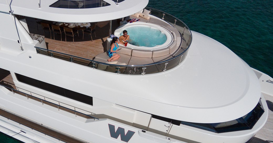 A charter guest sits in the Jacuzzi on the exterior of a superyacht with his girlfriend beside him