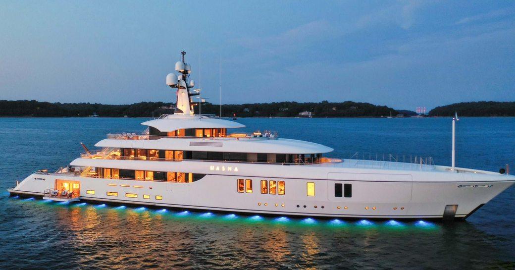 luxury yacht hasna underway at night, illuminated by lights