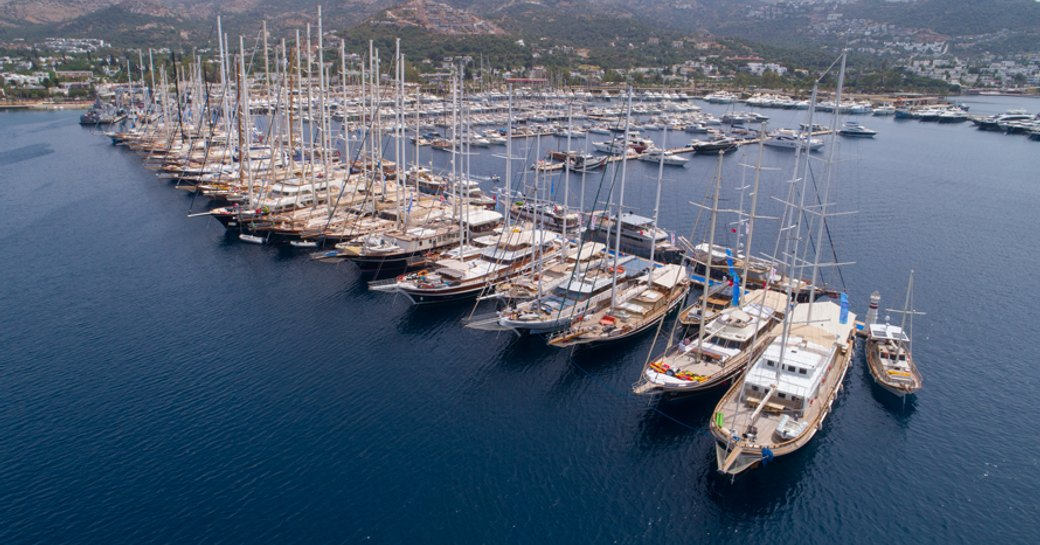 Sailing boats moored along pontoon at TYBA charter event, surrounded by sea.