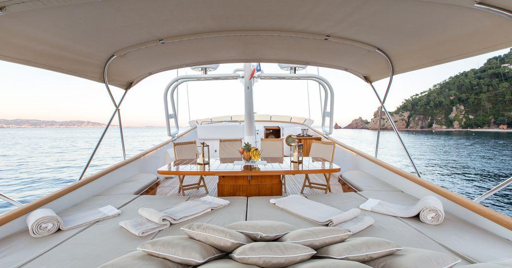 sunbathing area and alfresco dining area beyond on board motor yacht LIBERTUS