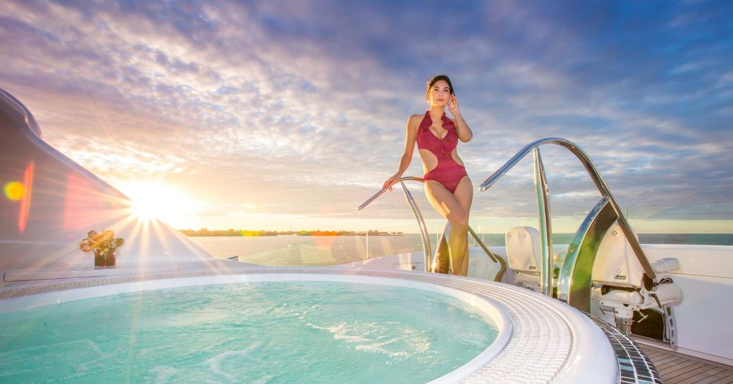 A charter guest besides the sundeck Jacuzzi featured on board luxury yacht USHER
