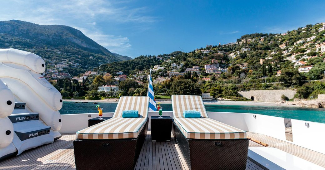 Sun loungers on sundeck of superyacht HEMILEA, with inflatable slide and views over the South of France coastline