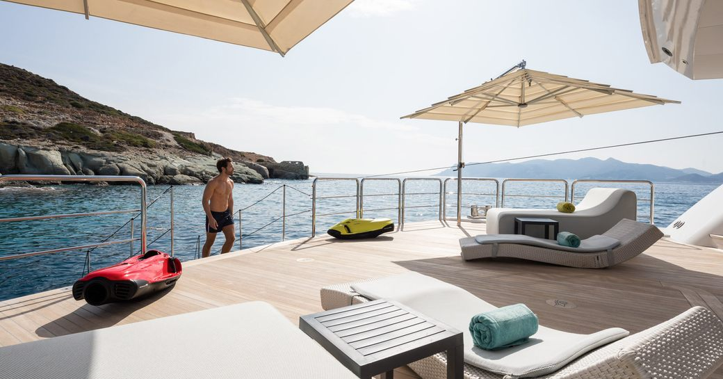 Man walking up to beach club on on superyacht O'PARI with sunloungers and teak decking