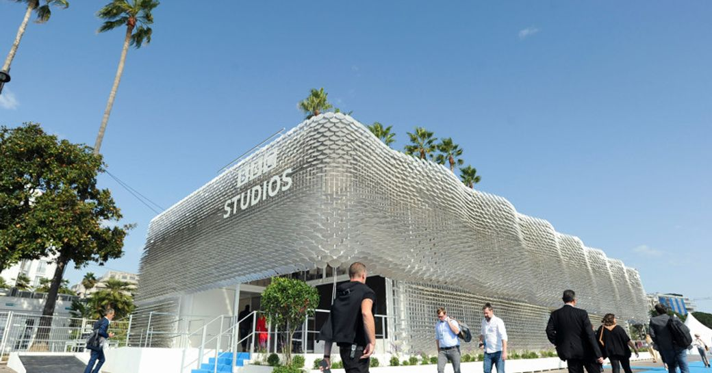 Exterior view of BBC Studios stand at MIPCOM, visitors walking along blue carpet outside.