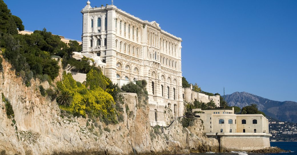 A sea-facing view of the Oceanographic Museum in Nice, a tall white building perched on the rock face