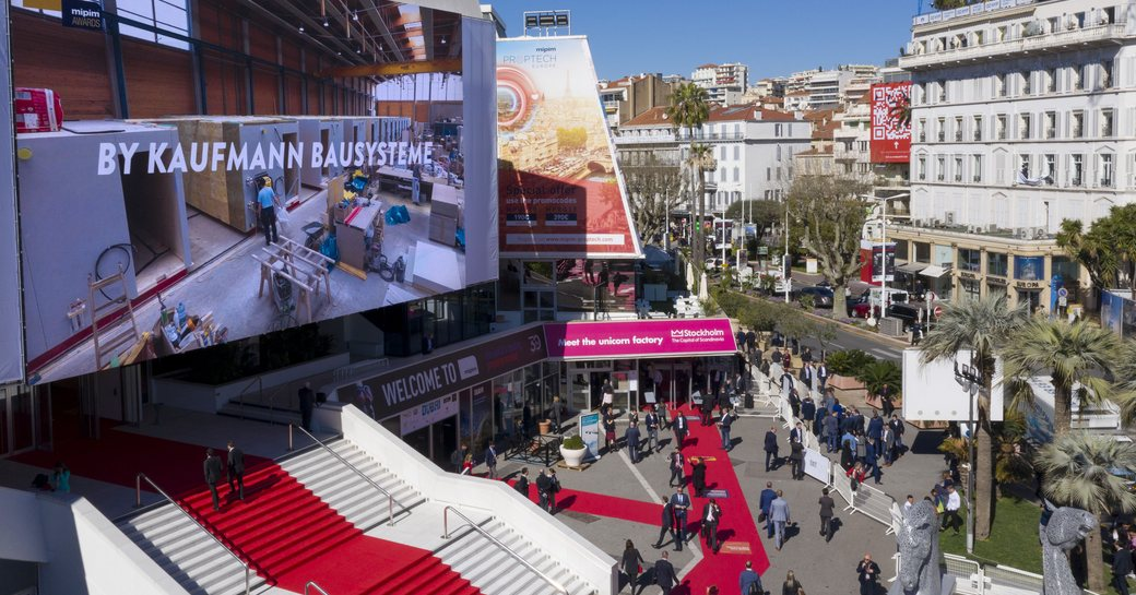 Red carpet entrance to MIPIM Cannes event, surrounded by Cannes infrastructure and visitors ascending steps.