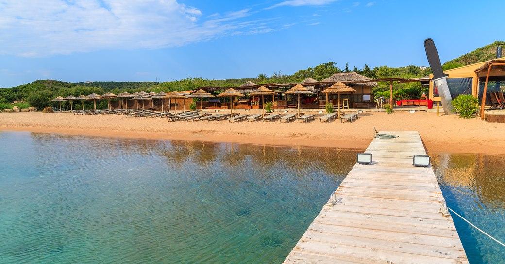 a beach along Santa Manza with a boardwalk and sun loungers