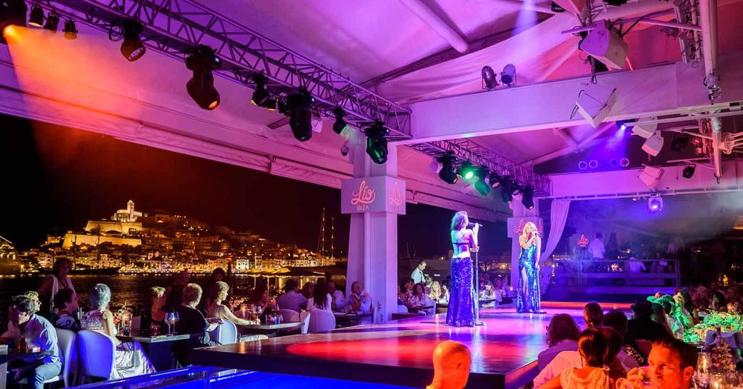 performers take to the stage in a busy venue in Ibiza, the Balearics