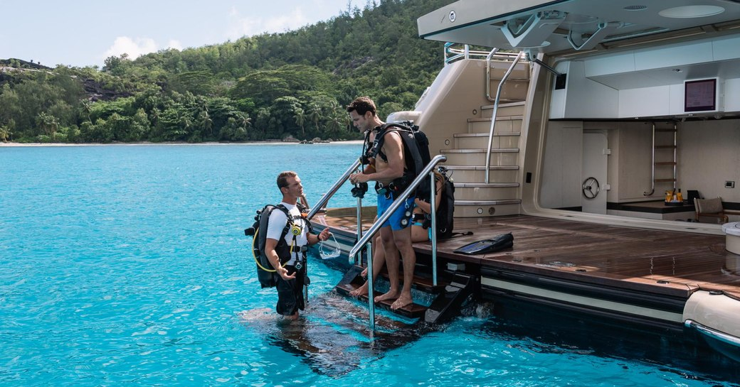 charter guest on swim platform of charter yacht LILI gets ready to go diving with crew member