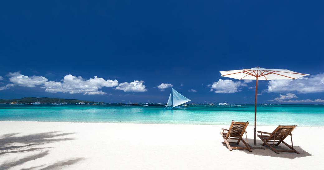 Long stretch of bright white sand beach in the Bahamas, with two deck chairs overlooking the sea