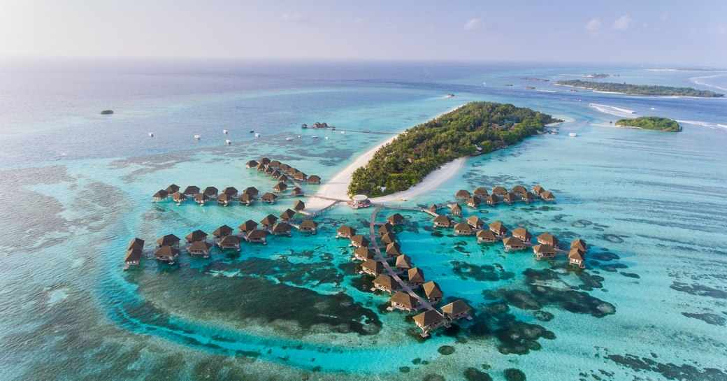 bungalows perched over the water and azure waters in the Maldives